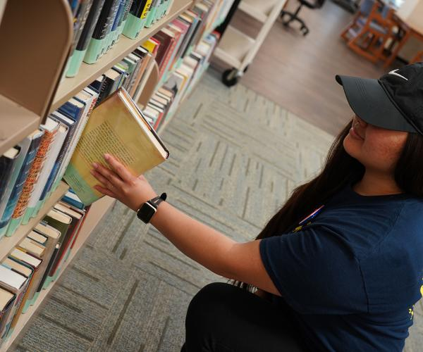 Student pulling popular reading book off shelf