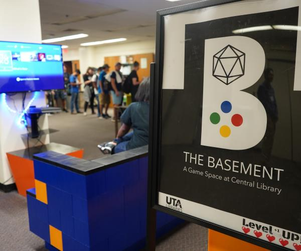 The logo for The Basement sits in the foreground while students play console games in the background at The Basement launch