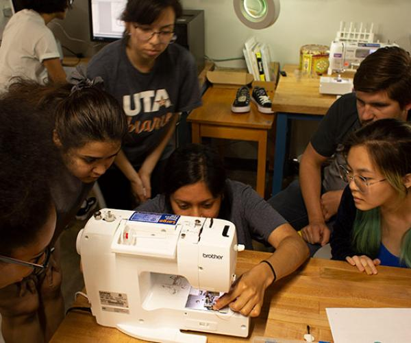 students gathered around FabLab sewing equipment
