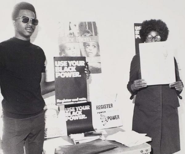 Two activists, one holding a Black Power poster